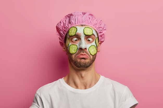 Jeune homme croise les yeux, applique un masque crème sur le visage avec du concombre, a une séance de beauté, porte un bonnet de bain