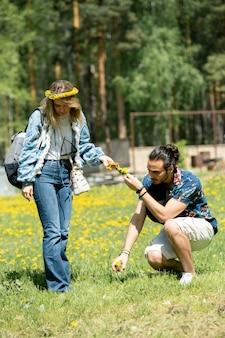 Jeune homme cueillant le pissenlit tout en faisant une clé à fleur pour petite amie en campagne