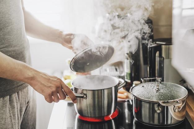 Jeune homme cuisinant des aliments frais à la maison et ouvrant le couvercle du pot fumant.