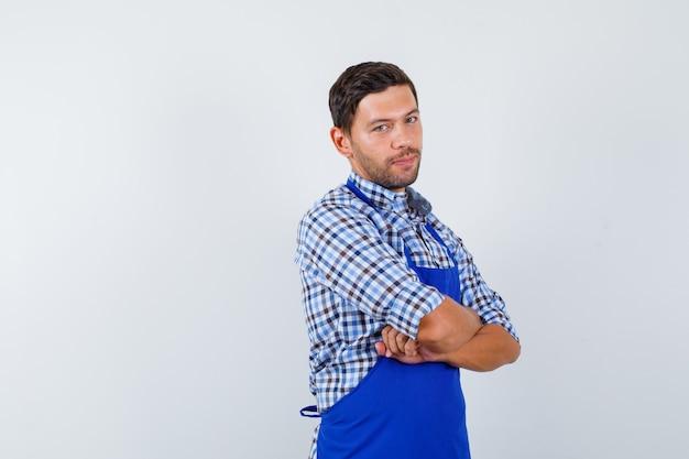 Jeune homme cuisinier dans un tablier bleu et une chemise
