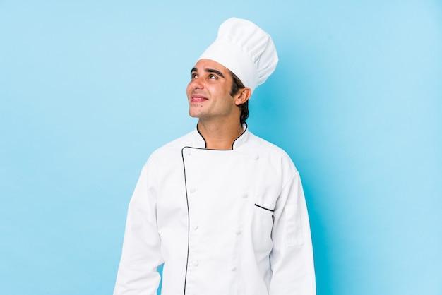 Jeune homme cuisinier isolé rêvant d'atteindre les objectifs et les buts