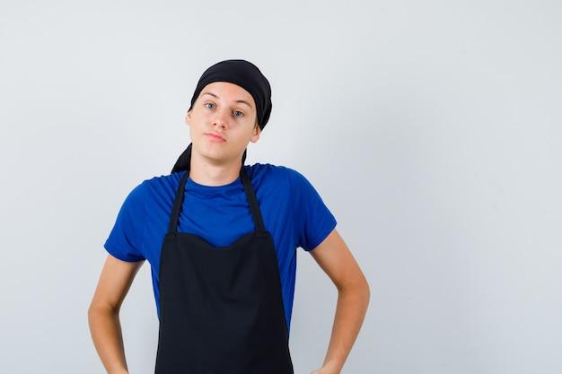 Jeune homme cuisinier avec les mains sur la hanche en t-shirt, tablier et l'air confiant. vue de face.