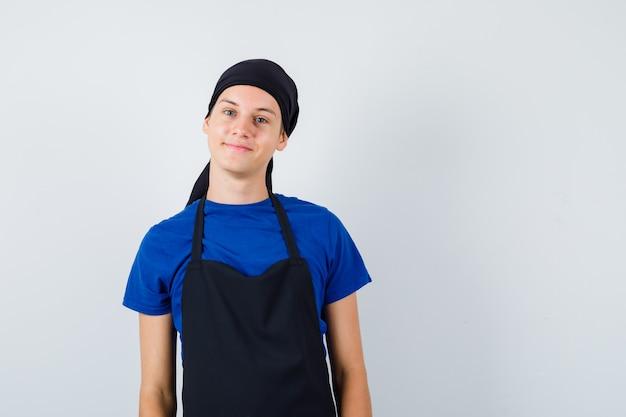 Jeune homme cuisinier posant debout en t-shirt, tablier et regardant gai, vue de face.