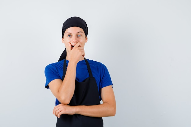 Jeune homme cuisinier en t-shirt, tablier avec la main sur la bouche et l'air étonné, vue de face.