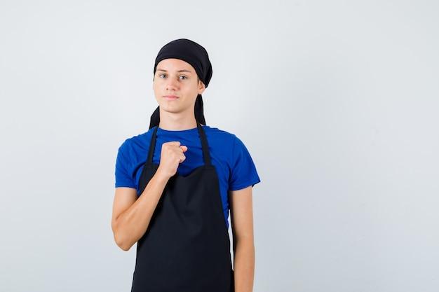 Jeune homme cuisinier en t-shirt, tablier avec poing fermé sur la poitrine et l'air confiant, vue de face.