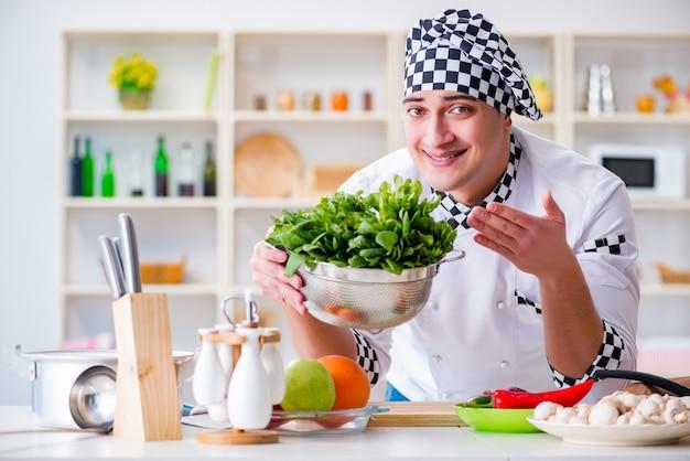 Jeune homme cuisinier travaillant dans la cuisine