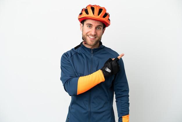 Jeune homme cycliste isolé sur fond blanc pointant vers le côté pour présenter un produit