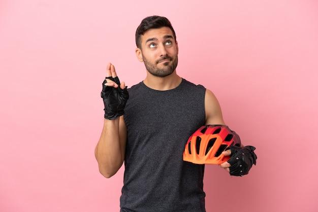 Jeune homme cycliste isolé sur fond rose avec les doigts croisés et souhaitant le meilleur