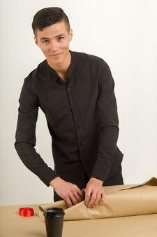 Jeune homme dans un bureau emballe un colis postal