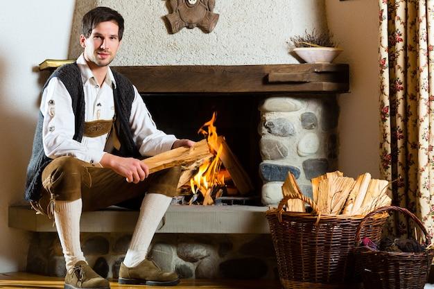 Jeune homme dans une cabane de montagne traditionnelle avec cheminée