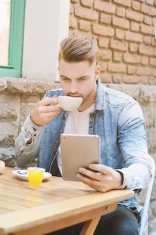Jeune homme dans un café café en utilisant une tablette.