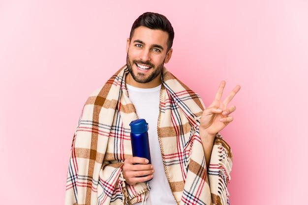 Jeune homme dans un camping isolé joyeux et insouciant montrant un symbole de paix avec les doigts.