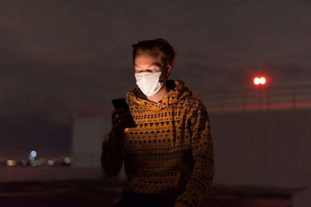 Jeune homme, dans, capuche, à, masque, utilisation, téléphone, dehors, pendant, orageux, soir