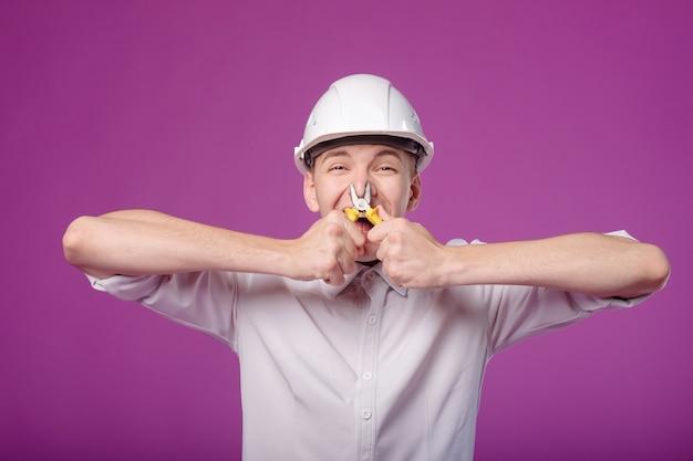 Le jeune homme dans le casque blanc sur le fond violet a serré son nez avec des pinces