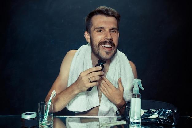Le jeune homme dans la chambre assis devant le miroir se gratte la barbe à la maison. concept d'émotions humaines et de style de vie