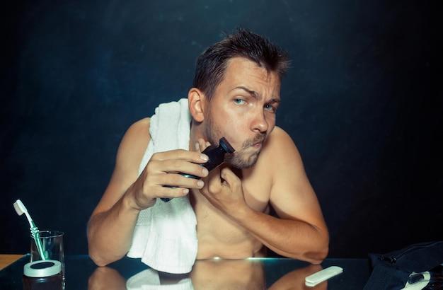 Le jeune homme dans la chambre assis devant le miroir se gratte la barbe à la maison. concept d'émotions humaines