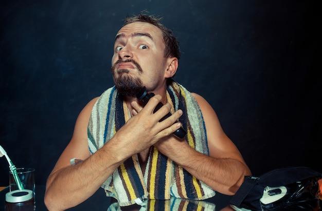 Jeune homme dans la chambre assis devant le miroir se gratter la barbe à la maison. émotions humaines et concept de mode de vie