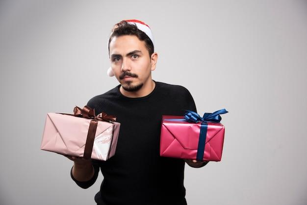 Un jeune homme dans un chapeau de père noël tenant des cadeaux du nouvel an.