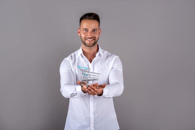 Un jeune homme dans une chemise blanche tenant un mini panier et debout sur fond gris
