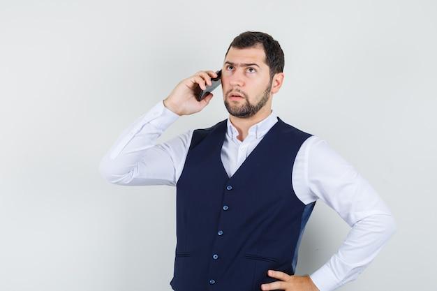 Jeune homme, dans, chemise, gilet, conversation téléphone mobile, et, sérieux