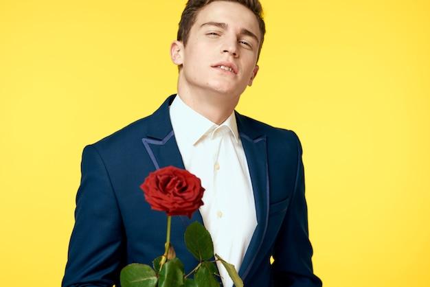 Jeune homme dans un costume classique avec une rose dans ses mains, look sexy