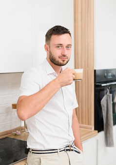 Jeune homme dans la cuisine avec un cappuccino