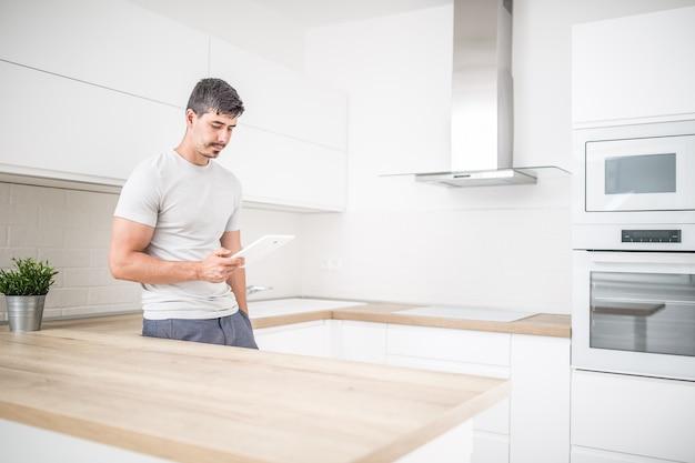 Jeune homme dans la cuisine à domicile avec tablette.