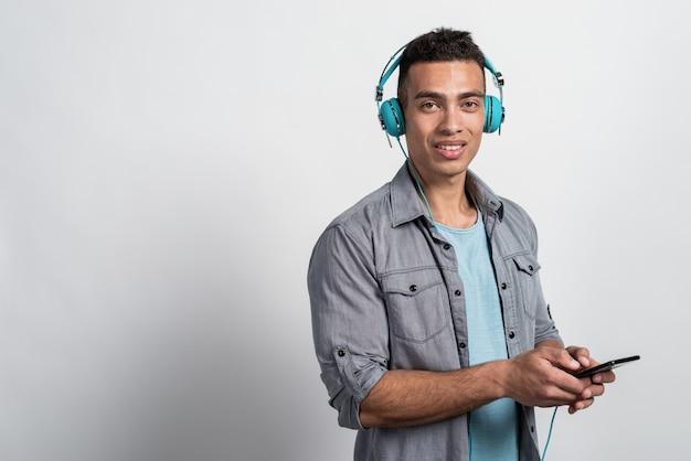 Jeune homme dans les écouteurs tenant le téléphone dans ses mains et en regardant la caméra