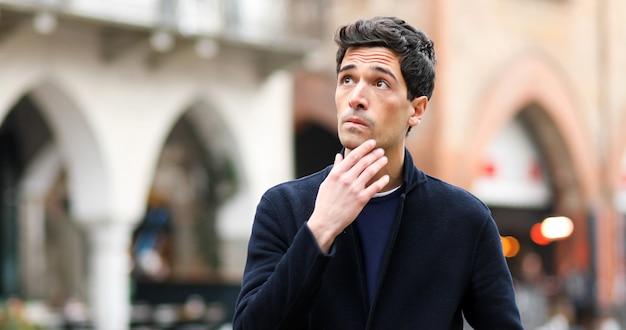 Jeune homme dans une expression réfléchie en plein air dans la ville