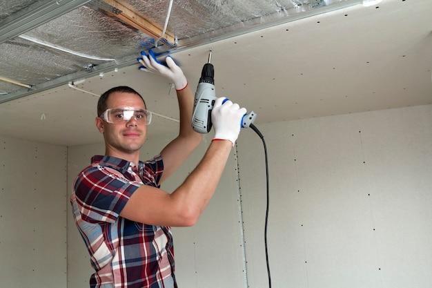 Jeune homme, dans, lunettes protectrices, fixation, cloison sèche, plafond suspendu, à, cadre métallique