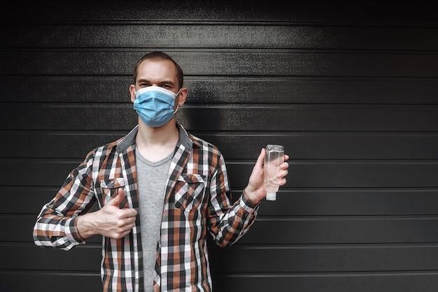 Jeune homme dans un masque médical tenant une bouteille avec un désinfectant antibactérien liquide