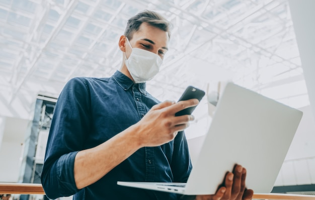 Jeune homme dans un masque de protection choisit un contact dans son smartphone