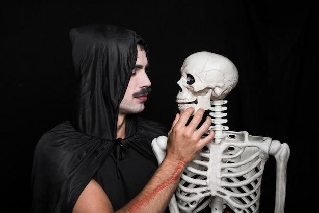 Jeune homme, dans, noir, manteau, à, capuche, regarder, squelette