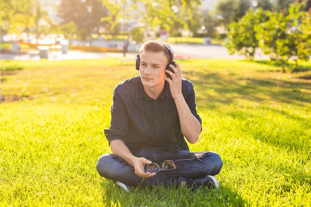 Jeune homme dans le parc, écoutez de la musique