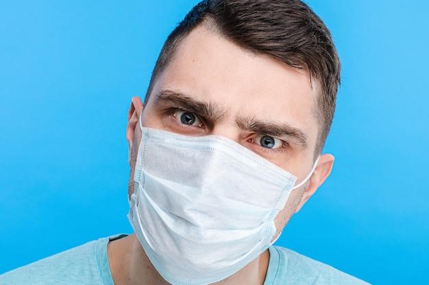 Jeune homme dans la peur du coronavirus debout dans un masque médical de protection