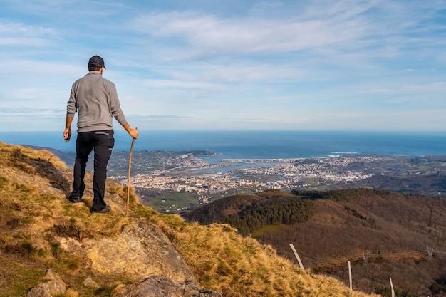 Un jeune homme dans un pull gris regardant la vue sur les villes de hondarribia et hendaya depuis les montagnes d'aiako harria ou peñas de aya, guipúzcoa