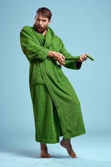 Jeune homme dans une robe verte isolée