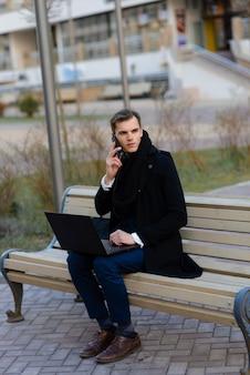 Jeune homme dans la rue et au café avec téléphone portable, ordinateur.