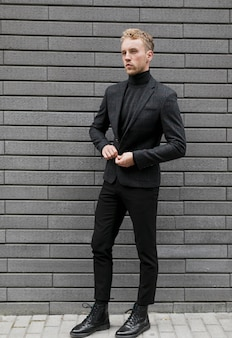 Jeune homme dans la rue fermant sa veste