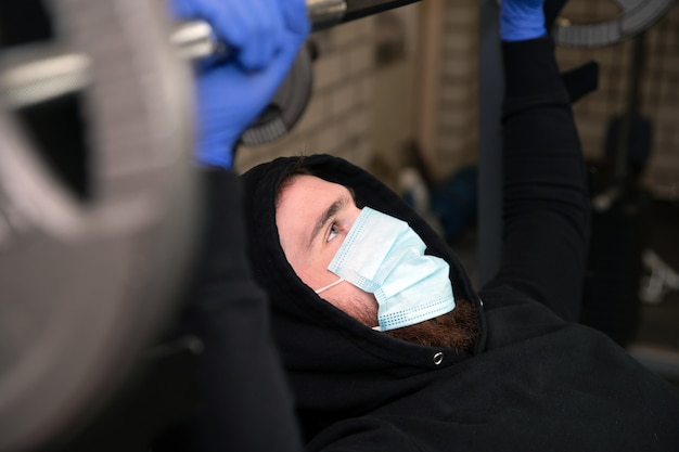 Jeune homme dans la salle de gym avec des poids et un masque de protection et des gants pour coronavirus, covid-19, fitness et corona concept