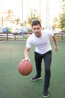 Jeune homme dans un t-shirt blanc jouant au basket