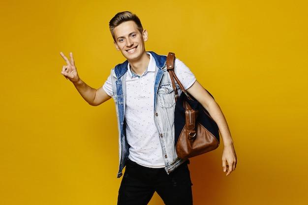 Un jeune homme dans une tenue en jean tient un sac de voyage et montre un geste de paix, isolé