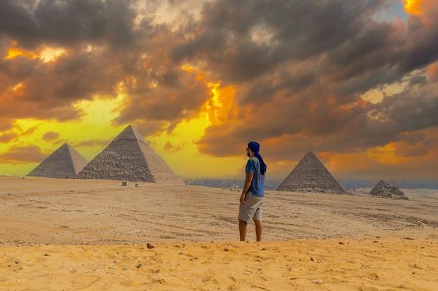 Un jeune homme dans un turban bleu marchant à côté des pyramides de gizeh
