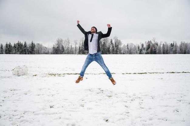 Jeune homme dans une veste d'affaires sautant joyeusement en l'air à l'extérieur dans une belle nature enneigée.