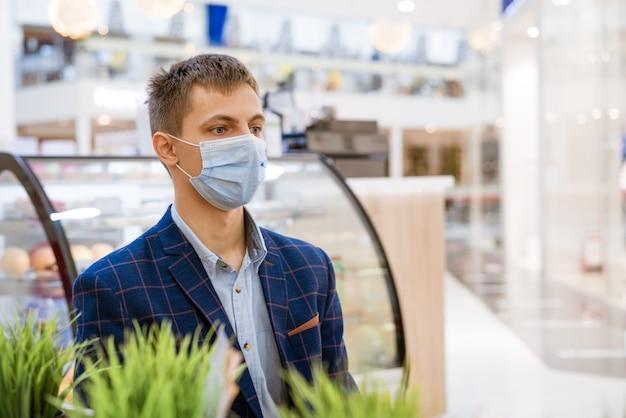 Un jeune homme dans une veste est assis dans un café dans un masque médical avec un téléphone à la main