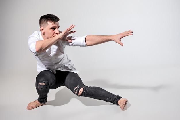 Le jeune homme dansant sur gris