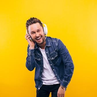 Jeune homme danse et écoute de la musique. émotions, expressions faciales, sentiments, langage corporel, signes. image sur un fond de studio jaune.