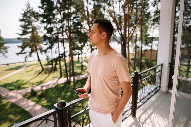 Un jeune homme debout sur le balcon tenant un téléphone portable