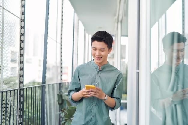 Jeune homme debout sur balcon textos sur téléphone mobile,