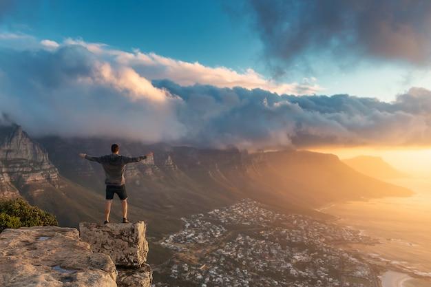 Jeune homme debout sur le bord au sommet de la montagne lion's head au cap avec une belle vue du coucher du soleil